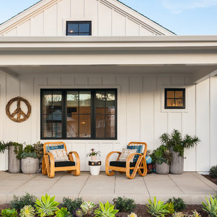 This is an example of a farmhouse concrete paver porch design in Orange County with a roof extension.