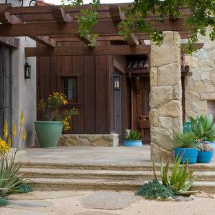 Tuscan stone front porch photo in Santa Barbara with a pergola