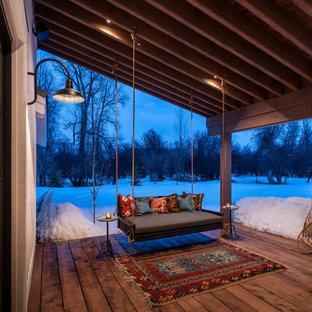 Esempio di un portico country con pedane e un tetto a sbalzo