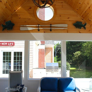This is an example of a mid-sized traditional screened-in back porch design in Boston with decking and a roof extension.