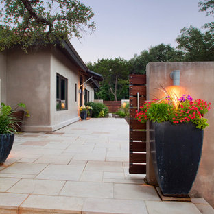 This is an example of a large industrial concrete paver porch design in Austin.