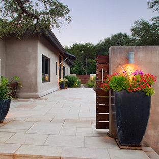Immagine di un grande portico industriale davanti casa con un giardino in vaso e pavimentazioni in cemento