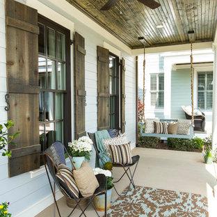 Idée de décoration pour un porche champêtre avec une dalle de béton et une extension de toiture.
