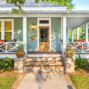 Idée de décoration pour un grand porche avant tradition avec une terrasse en bois et une extension de toiture.