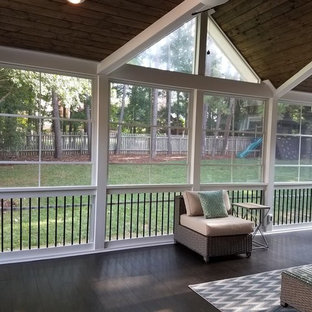 Mid-sized transitional screened-in back porch idea in Charlotte with decking and a roof extension