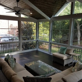 This is an example of a mid-sized transitional screened-in back porch design in Charlotte with decking and a roof extension.