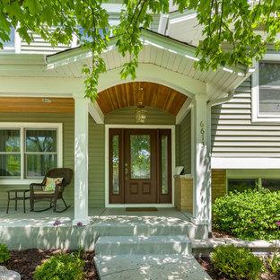 Ispirazione per un portico tradizionale di medie dimensioni e davanti casa con lastre di cemento e un tetto a sbalzo