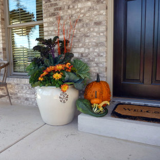На фото: с невысоким бюджетом маленькие веранды на переднем дворе в стиле кантри с растениями в контейнерах, покрытием из бетонных плит и навесом