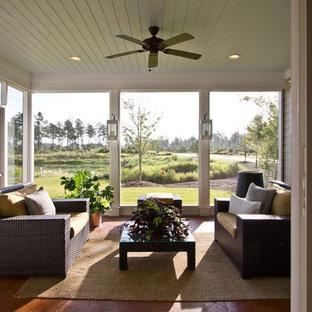 Immagine di un grande patio o portico chic dietro casa con piastrelle, un tetto a sbalzo e un portico chiuso