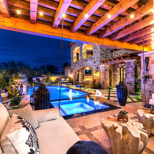 Inspiration for a huge industrial stone back porch remodel in Phoenix with a fire pit and an awning
