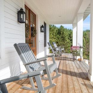 Exempel på en stor lantlig veranda framför huset, med trädäck och takförlängning