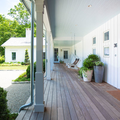 Mid-sized cottage front porch idea in New York with decking and a roof extension