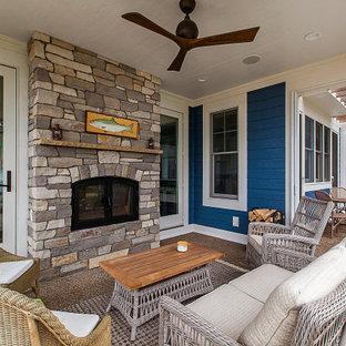Idee per un portico stile marino di medie dimensioni con un tetto a sbalzo e un caminetto