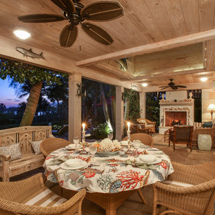 Island style tile back porch idea in Miami with a fireplace and a roof extension
