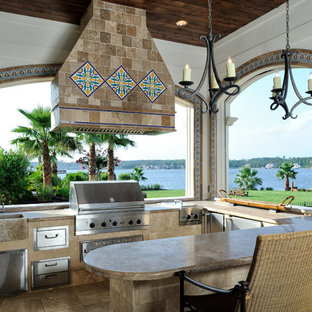 Design ideas for a mediterranean veranda in Houston with an outdoor kitchen, tiled flooring and a roof extension.