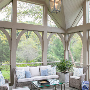 Large classic stone screened-in back porch idea in Milwaukee with a roof extension