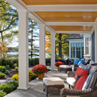 Large elegant stone front porch photo in Boston with a roof extension