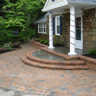Large trendy concrete paver porch idea in Philadelphia with a roof extension