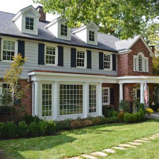 Immagine di un portico chic di medie dimensioni e davanti casa con pavimentazioni in pietra naturale e un tetto a sbalzo