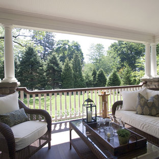 Large classic front porch idea in New York with a roof extension and decking