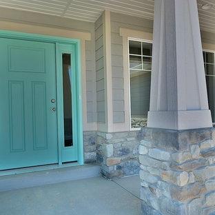 Immagine di un piccolo portico stile americano davanti casa con lastre di cemento e un tetto a sbalzo