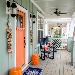 This is an example of a mid-sized beach style front porch design in Wilmington with a roof extension and decking.