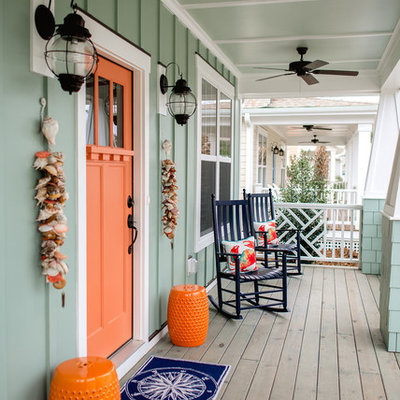 This is an example of a mid-sized coastal front porch design in Wilmington with a roof extension and decking.