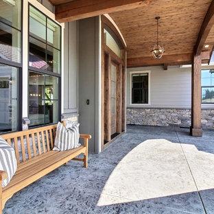 Ispirazione per un ampio portico american style dietro casa con cemento stampato e un tetto a sbalzo