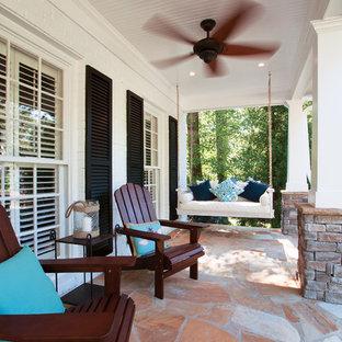 Foto di un grande portico stile americano davanti casa con pavimentazioni in pietra naturale e un tetto a sbalzo
