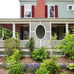 Foto di un grande portico chic nel cortile laterale con pavimentazioni in pietra naturale e un tetto a sbalzo