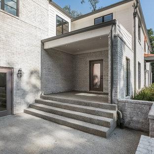 Ispirazione per un grande portico minimalista davanti casa con lastre di cemento e un tetto a sbalzo