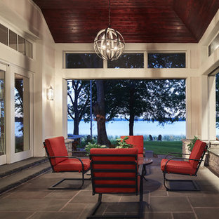 This is an example of a large transitional stone screened-in side porch design in Minneapolis with a roof extension.