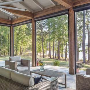 Country tile screened-in back porch idea in New Orleans with a roof extension