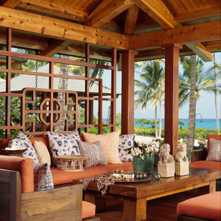 Island style porch idea in Hawaii with a roof extension and decking