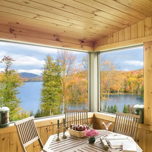 Large mountain style screened-in back porch idea in Burlington with decking and a roof extension