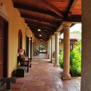 Ispirazione per un ampio portico american style davanti casa con piastrelle, un giardino in vaso e un tetto a sbalzo
