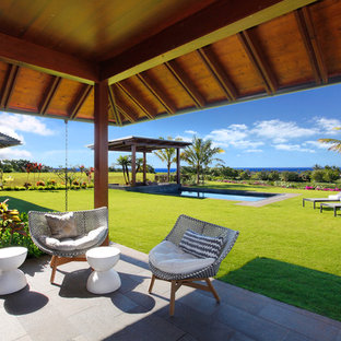 Ejemplo de terraza tropical, de tamaño medio, en patio trasero y anexo de casas