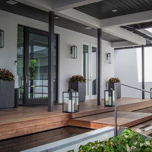 Esempio di un grande portico moderno davanti casa con pedane e un tetto a sbalzo