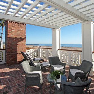 Idéer för att renovera en maritim veranda, med marksten i tegel och takförlängning