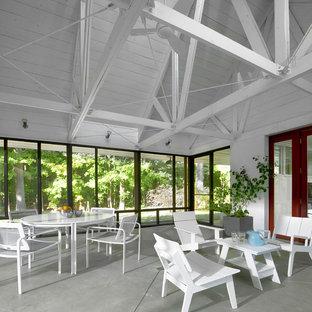 Idee per un piccolo patio o portico industriale davanti casa con un portico chiuso, lastre di cemento e un tetto a sbalzo