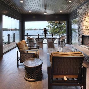 Idée de décoration pour un grand porche arrière design avec un foyer extérieur, du carrelage et une extension de toiture.