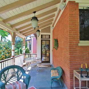 This is an example of a traditional concrete front porch design in Philadelphia with a roof extension.