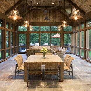 Ispirazione per un ampio portico stile rurale con pavimentazioni in pietra naturale, un portico chiuso e un tetto a sbalzo