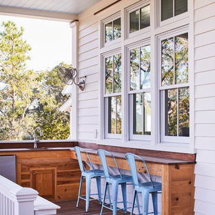 This is an example of a beach style outdoor kitchen porch design in Charleston with decking and a roof extension.