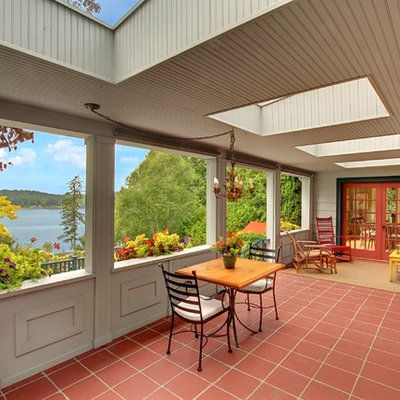Country tile porch photo in Seattle with a roof extension