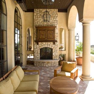 Modelo de terraza mediterránea, grande, en anexo de casas y patio trasero, con chimenea y adoquines de ladrillo