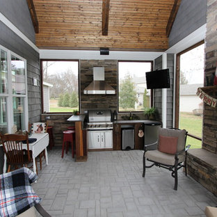 Mid-sized arts and crafts stamped concrete porch idea in Nashville with a roof extension