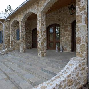 Immagine di un grande portico boho chic davanti casa con pavimentazioni in cemento e un tetto a sbalzo