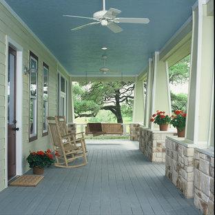 Foto di un grande portico country davanti casa con pedane e un tetto a sbalzo