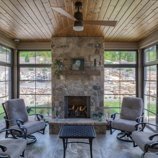 Large classic tile back porch idea in Other with a fireplace and a roof extension